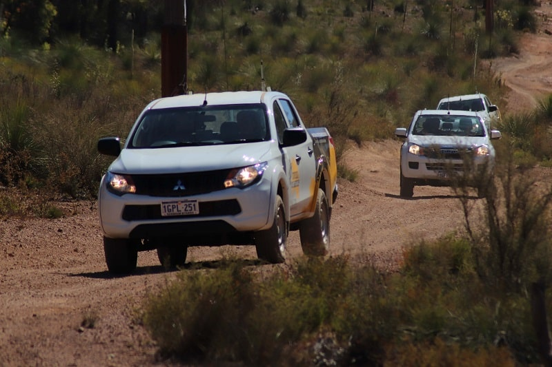 3 4WD's travelling on a sand track.