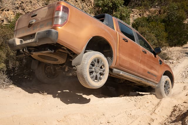 """""""Orange-brown 4WD on an off road track that represents """"best 2019 dual-cab 4wd ute """""""" blog."""""""