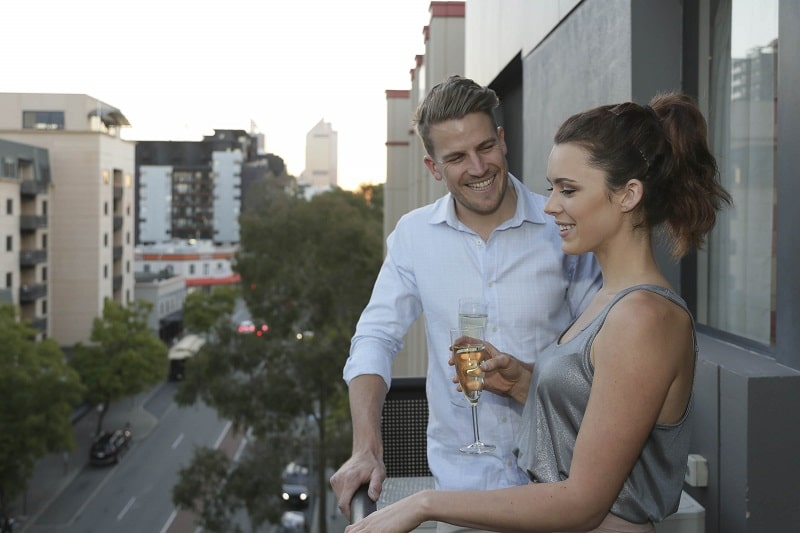 Couple having a drink on the balcony of Mont Clare Apartment.