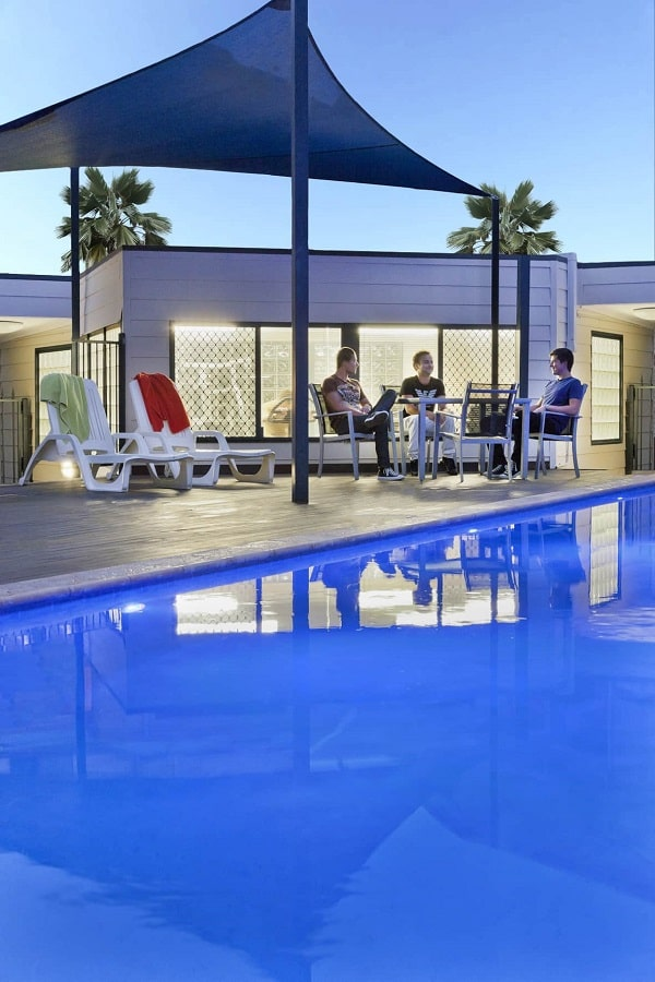3 men sitting and talking beside a swimming pool of the Mont Clare Apartments.