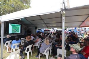 Group of people sitting on big tent and listening to a 4WD forums.