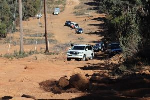 A team of 4WD vehicles/trucks travelling as a convoy in an off-road track.