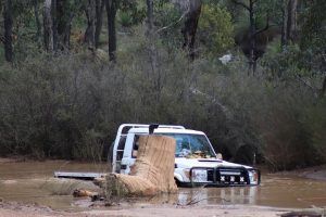 White 4WD truck travelling/crossing on a watery track.