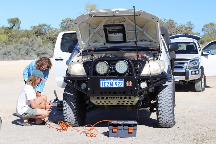2 women checking the tyre pressure on their 4WD.