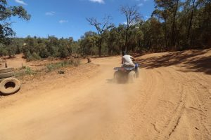 Man driving on a quad bike or side-by-side vehicle at a sand track.